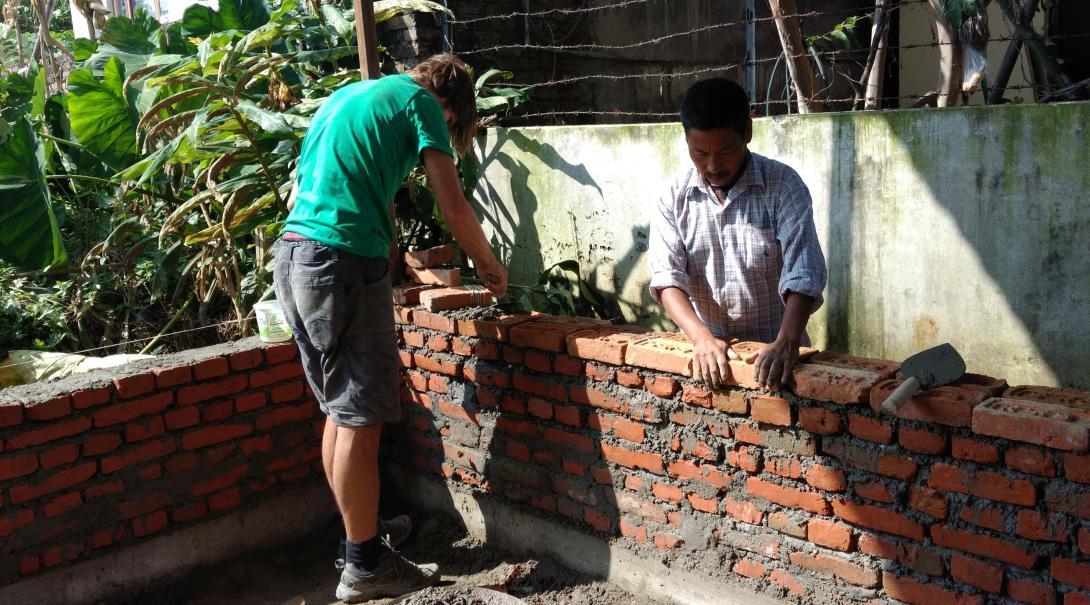 Voluntario y obrero nepalí trabajando juntos en la construcción de un muro en Nepal.